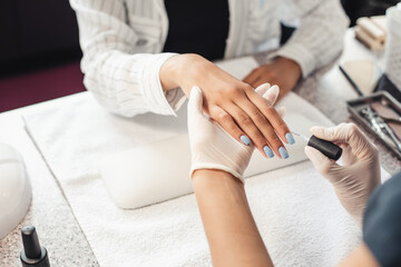 Reopening of beauty salon and nail care after quarantine. Manicure master in rubber gloves paints nails with blue gel polish to african american lady client