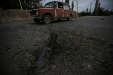 A car drives past the remains of spent ammunition following a recent shelling in Tartar