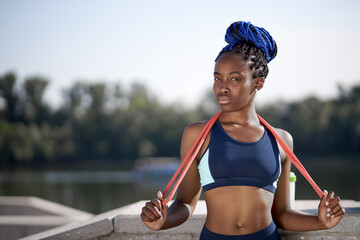 portrait of sweaty afro american fit woman with skipping rope, jumping running and jogging concept