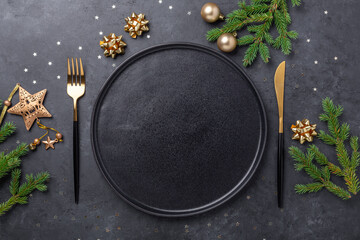 Christmas table setting with empty black ceramic plate, fir tree branch and gold accessories on...