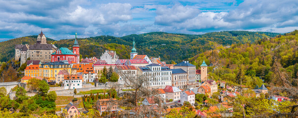 Aerial panoramic view of medieval Loket town with Loket Castle Hrad Loket gothic style on massive rock, colorful buildings. Panorama of Loket town and forest hills in autumn, Czech Republic