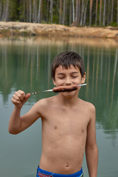 a boy on nature in the forest eats a sausage on a stick