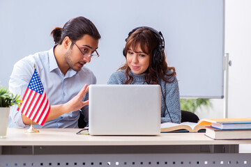 Young female student and male english teacher in the classroom