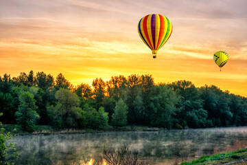A beautiful sunrise over the river with a hot air balloons in the sky in the early morning.
