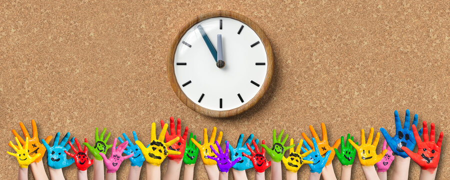 painted kids hands with smiley emoticons in front of cork background with a clock
