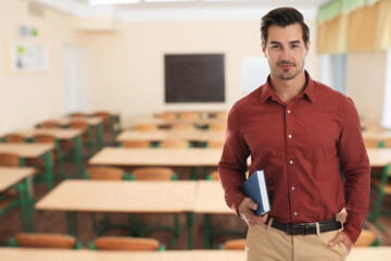 Young school teacher waiting for students in classroom