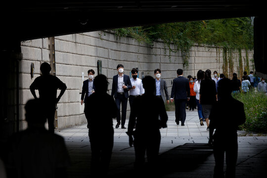 Pedestrians wearing masks walk amid the coronavirus disease (COVID-19) outbreak at the Cheonggye stream in Seoul