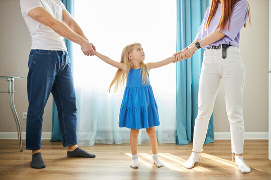 sad daughter feeling upset about parents divorce, caucasian child girl suffer from trauma offended by fights conflicts shared custody, child girl between man and woman