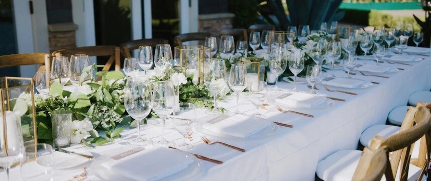 Wedding banquet with clear glass goblets and wine glasses, white plates and gold forks and decorations