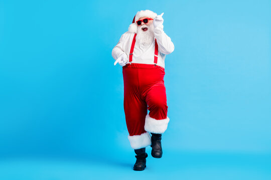 Full size photo of funky fat crazy santa claus with big abdomen beard dance x-mas christmas holly party club wear suspenders overalls sunglass boots isolated blue color background