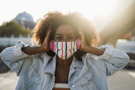 Black girl listening music with headphones while wearing face mask outdoor - Coronavirus lifestyle concept