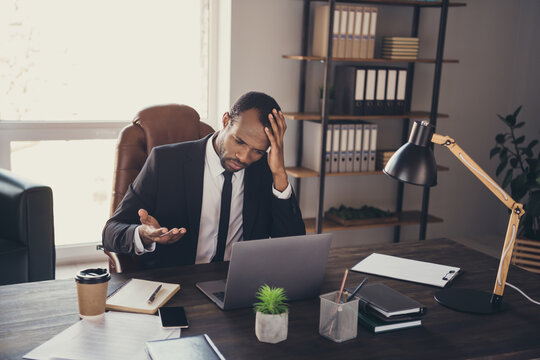 Portrait of frustrated afro american man ceo representative agent sit desk work laptop cant solve start up development progress career dilemma in workstation workplace