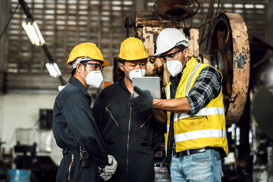 team engineer mechanic man wearing protective face mask and checking plan on tablet for maintenance metal machine at factory, teamwork concept