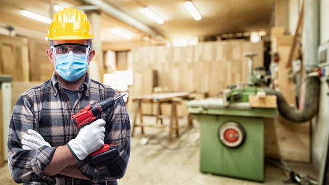 Carpenter worker in the carpentry workshop, wears helmet, goggles, leather gloves and surgical mask to prevent coronavirus infection. Preventing Pandemic Covid-19 at the workplace.