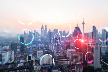 Hologram of abstract technology glowing icons, panoramic cityscape of Kuala Lumpur at sunset, Malaysia, Asia. The concept of worlds technological changes. Double exposure.