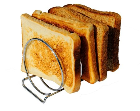 Four slices of toast in a metal coiled toast rack.