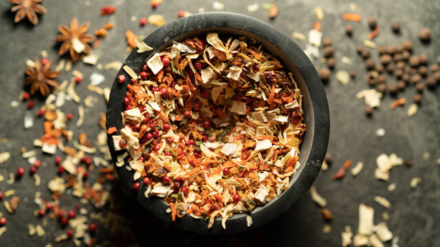 TOP VIEW: Grinding spices herbs in a mortar on a table