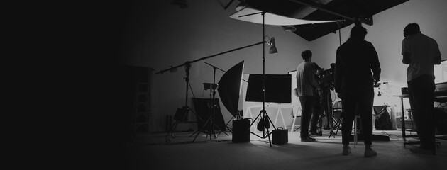 Fototapeta Behind the scene of photo shooting and production set up in the big studio. Professional crew team working and camera equipment in silhouette. such as light box, tripod, flashlight. and copy space. obraz