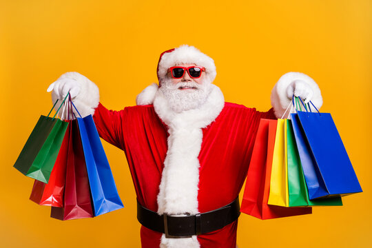 Portrait of his he nice attractive cheerful cheery fat Santa holding in hands carrying things buyings retail store boutique black Friday isolated bright vivid shine vibrant yellow color background