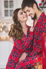A couple in red christmas pajamas in the christmas decorated kitchen