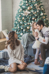 Happy family in christmas decorations. Mother father and little daughter in day time cozy christmas atmosphere