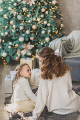 Pretty little girl and beautiful mother in white sweaters hug near christmas tree and make hairstyle together