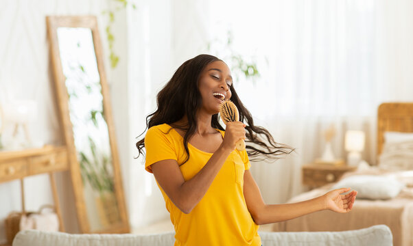 Joyful black lady with hairbrush as microphone singing and dancing at home