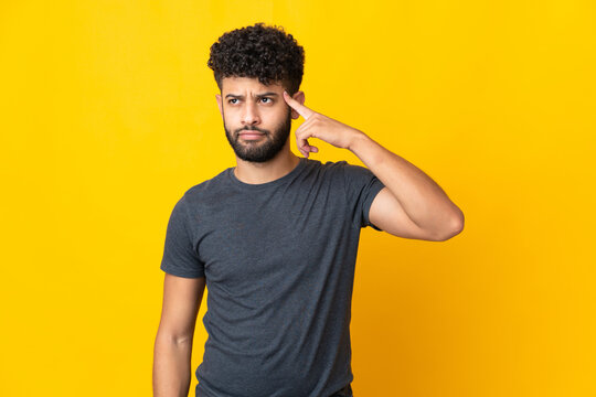 Young Moroccan man isolated on yellow background making the gesture of madness putting finger on the head