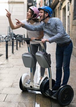 young couple guy and girl walking on segway in streets of european city