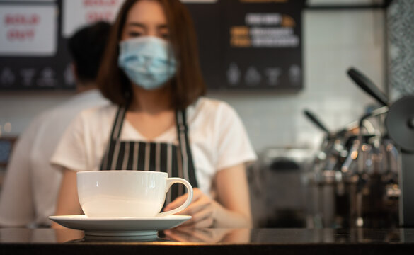 Selective focus of coffee cup and background of Asian barista woman wearing face masks to prevent contagious diseases and serve to customers in the coffee shop. The concept of prevention from COVID 19