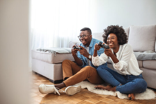 Photo of young couple playing video games at home. They are friendly competitors. Cute Teenage Couple Playing Video Games on Date Night. Beautiful couple playing video games on console