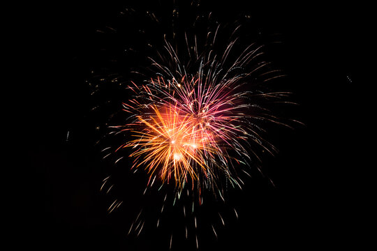 Red orange and yellow fireworks in the night sky