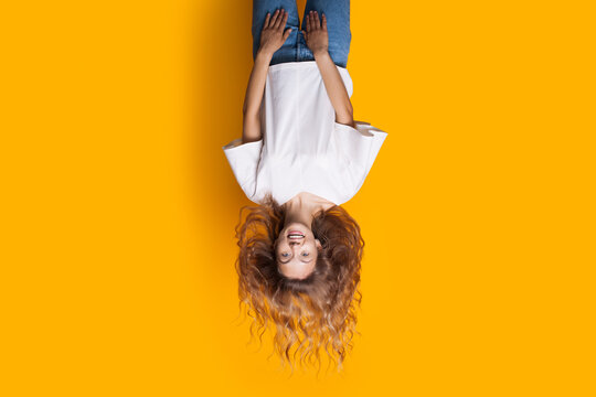 Upside-down photo of a blonde lady in jeans and white t-shirt smiling at camera and advertising something