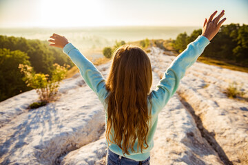 Happy traveler girl standing with raised arms and enjoying a beautiful nature. Freedom feel good...