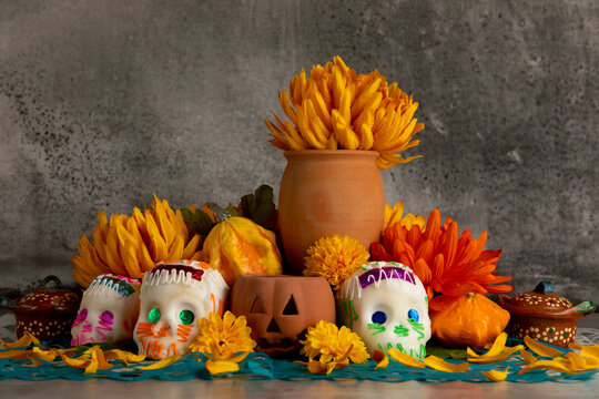 """Sugar skulls used for """"dia de los muertos"""" celebration in a grey background with cempasuchil flowers"""