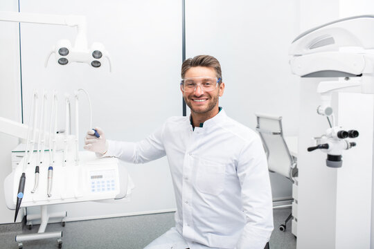 Confident male dentist sitting in a modern clinic near his dental chair. Dental hygienist wearing protective glasses smiling at the camera