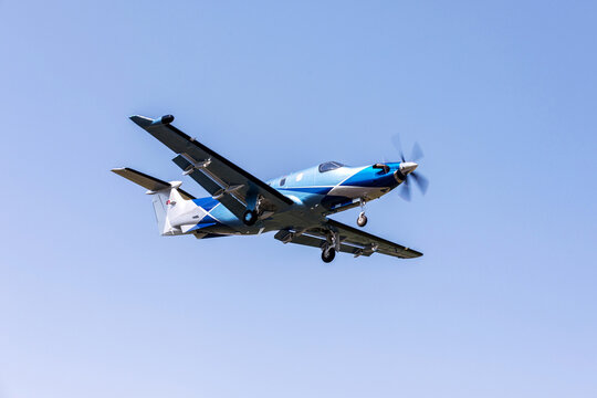 Single-engine blue airplane flying on a sunny day in the blue sky. The plane rises after takeoff.