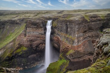 Svartifoss, Black Waterfall, Iceland.Waterfall falling on stones through autumn forest. Fall nature specification. landscape with powerful falls on the mountain river