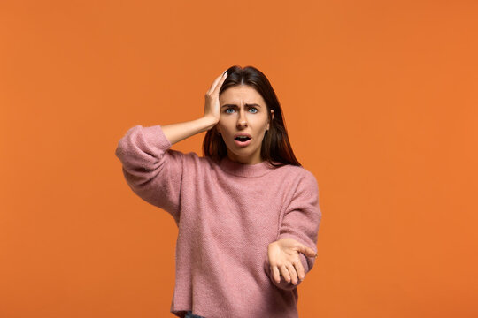 What have you done. Portrait of stunning beautiful woman in pink sweater keeps one palm rised and another on head, looking with popped out eyes and opened mouth. cant understand what to do