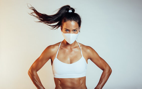Muscular sports woman with face mask