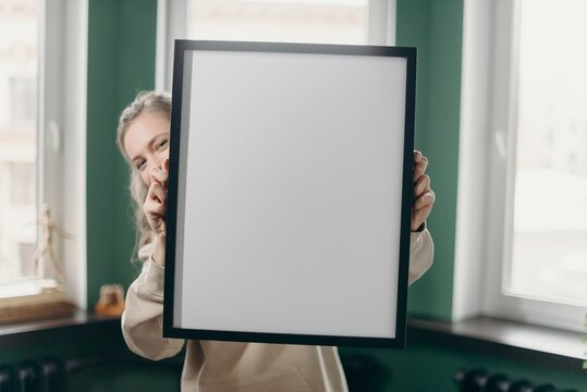 Portrait Of Woman Holding Frame At Home