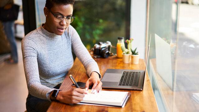 Focused black woman writing in notebook