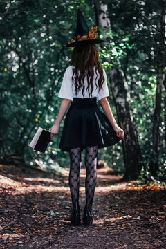 Young pretty witch in black hat close up in the forest. Whitch halloween cosplay. Art processing.