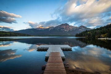 Sunrise over Pyramid Lake and the dock, with the mountains, clouds and trees reflected in the water (Jasper, Alberta, Canada)