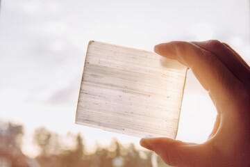 Person holding natural mineral stone Selenite plate against sun and blue sky, stone has healing and cleansing properties. Also used for recharging other mineral crystal stones.