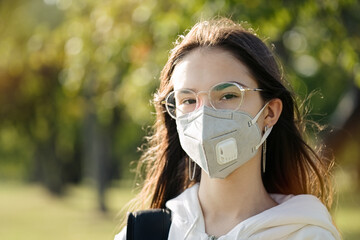 Portrait of cute teenager girl wearing protective mask. Health care and education concept