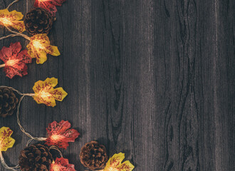 background with leaves Autumn garland with leaves and cones on the left on a black wooden table with space for text on the right, top view close-up. Wall mural