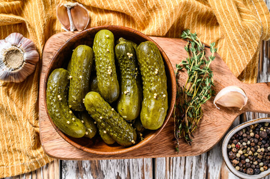 Marinated cucumbers gherkins in wooden plate. Pickles with mustard and garlic. White background. Top view