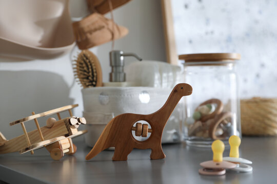 Wooden toys and pacifiers on grey table in child room