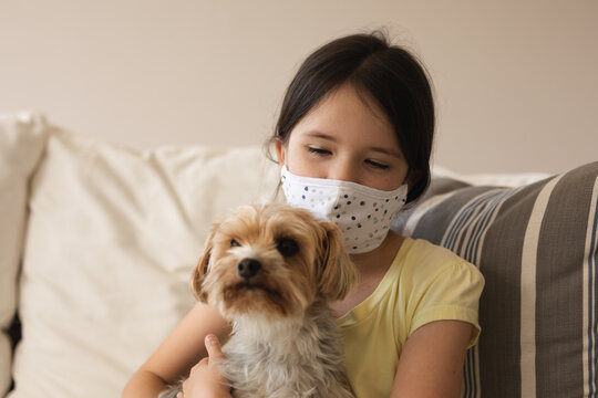 Girl wearing face mask holding her pet dog at home